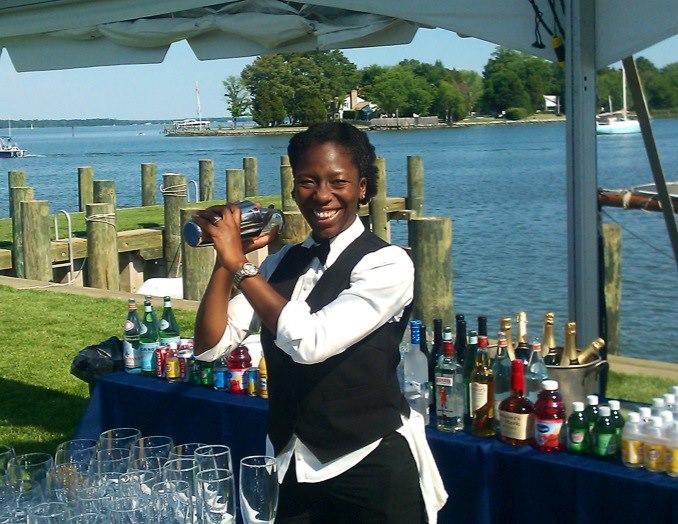 Dionne bartending at a beach party